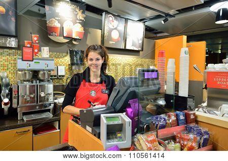 GENEVA, SWITZERLAND - NOVEMBER 18, 2015: barista in Starbucks Cafe. Starbucks Corporation is an American global coffee company and coffeehouse chain based in Seattle, Washington