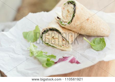 a healthy wrap with turkey, greens and cheese made with whole grain tortilla wrap on white wrapping paper, selective focus poster