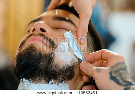 Crafty master. Close up of open razor in hands of professional barber shaving beard of his client poster