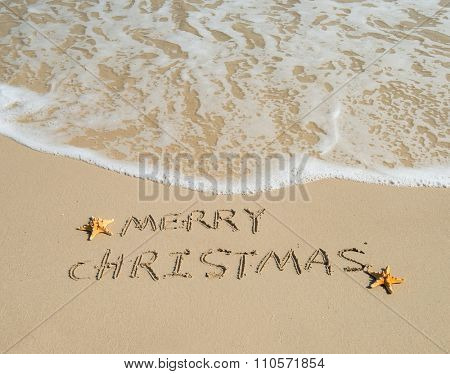 Merry Christmas written on tropical beach white sand