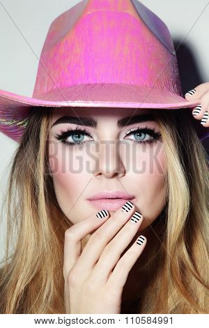 Portrait of young beautiful blonde girl with stylish make-up and manicure in party pink cowboy hat