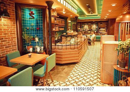 Interior Of Modern Style Cafe With Tiled Walls And Design Furniture