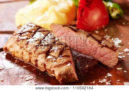 steak and side dishes on a wooden plate