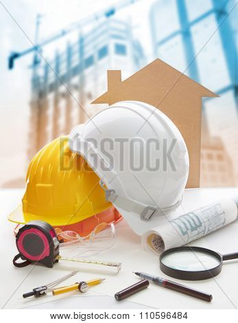 safety helmet blue print plan and construction equipment on architect engineer working table with building construction crane background use for construction industry business and civil engineering poster