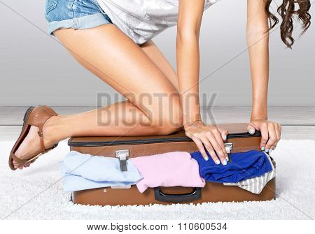 Young  woman packing suitcase, trying to close it