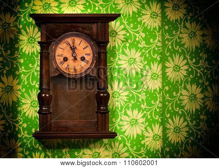 Old vintage wooden wall clock hanging on green wall