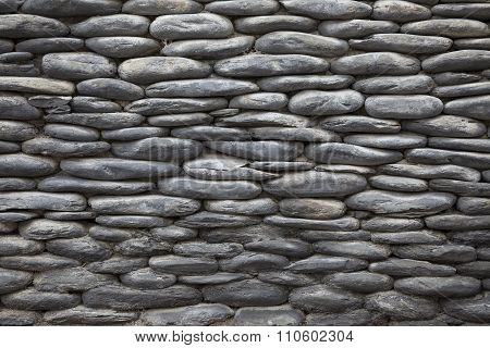 Gray stone background of the old wall of pebbles