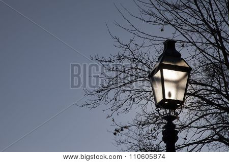 Old street lamp against dramatic blue sky