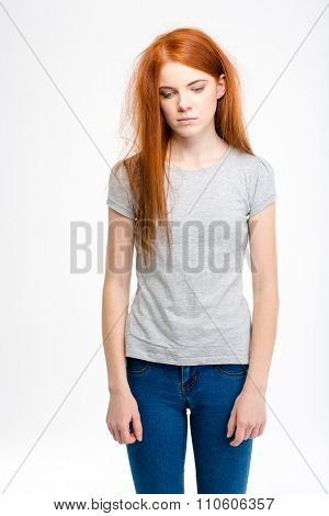 Portrait of sad exhausted young redhead girl with long tousled hair isolated over white background