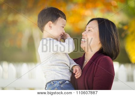 Happy Chinese Mom Having Fun and Holding Her Mixed Race Little Boy.
