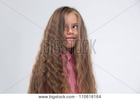 Portrait of a little girl with long hair making silly face isolated on a white background