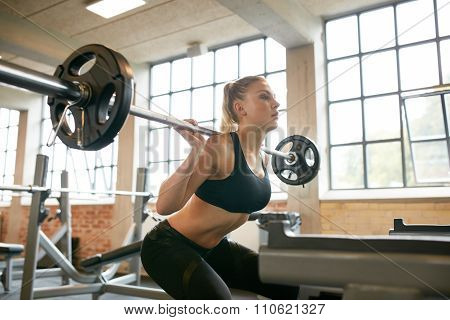 Female Exercising In Gym Doing Squats