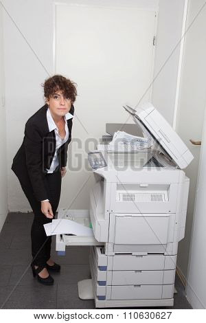 Woman Copying Notes On A Coin Operated Photocopier