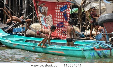 Siem Reap Cambodia Oct 28 2015 : Children swimming in the murky waters of the Tonle Sap River jumping from boat on October 282015