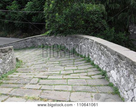 Descent stone walkway of medieval bridge known as Ponte del Diavolo in Borgo a Mozzano Italy poster