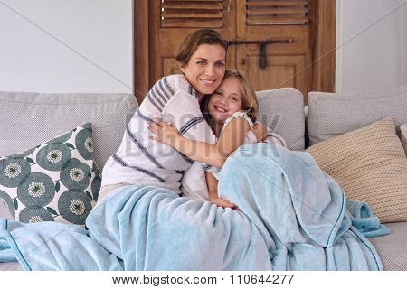 happy caucasian mother hugging cuddling her daughter sitting on the coach all snuggled with a blanket love