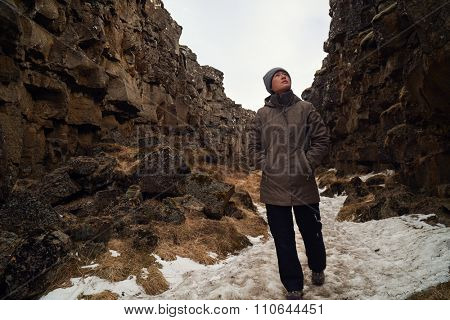 Independent woman tourist exploring the crack between tectonic plates in Thingvellir national park, Iceland