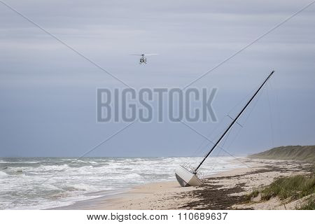 Helicopter Flying Over A Stranded Sailboat On A Florida Beach