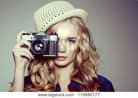 Young woman with camera. Blonde in a plaid shirt. Hipster fashion photographer girl. Young people, youth culture poster