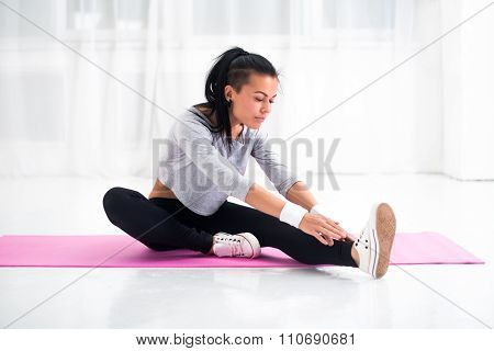 Fit woman doing aerobics gymnastics stretching exercises her leg and back to warm up at home on yoga mat poster