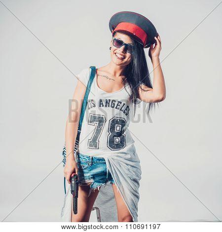 Fashion swag girl holding gun woman having fun wearing police cap