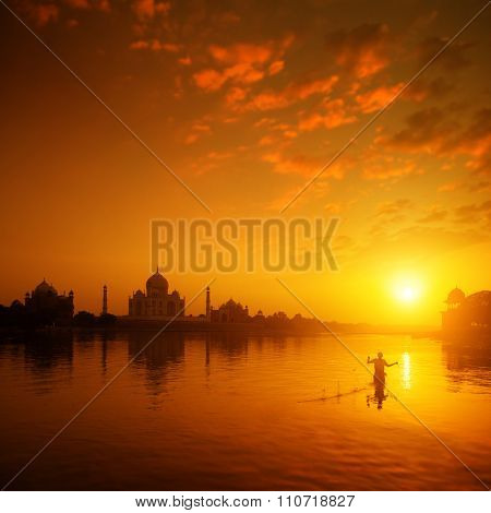 Taj Mahal in Agra, India in golden sunset with silhouette of fisherman.