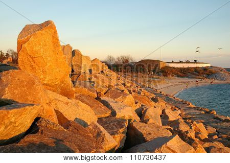 Setting sun causes dike rocks to glow at historic Fort Phoenix in Fairhaven Massachusetts poster