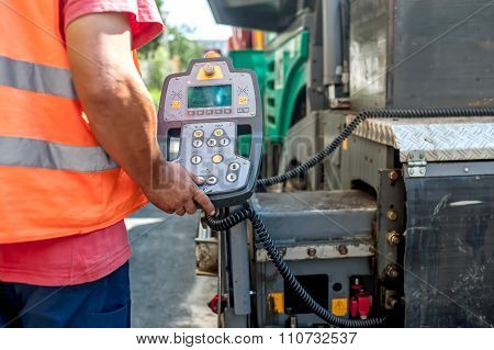 Close Up Of Worker Hand Operating Asphalt Paver Machinery On Construction site of road works
