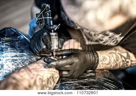 Artist At Tattoo Shop Drawing With Ink On Skin Of Client