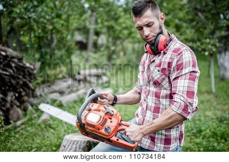 Portrait Of Sexy And Hansome Man With Chainsaw And Protective Ge