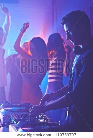 Male deejay mixing sounds on background of dancing girls