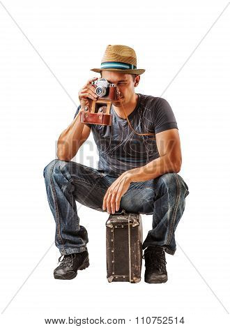 Young Man Traveler Takes A Shot While Sitting On Suitcase Over W