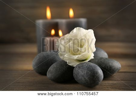 Alight wax grey candle with pebbles and beautiful flower on wooden background poster