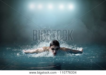 Swimmer in waterpool. Butterfly style of swimming.