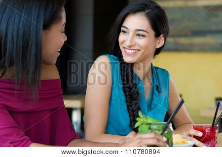 Closeup shot of smiling young woman holding cocktail. Two female friends smiling and drinking cocktails at happy hour. Portrait of beautiful young girl chatting during the cocktail party.