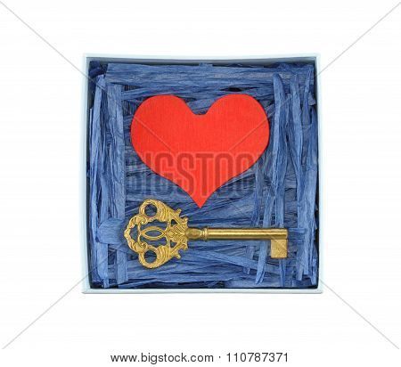 Red painted wooden heart and bronze key enclosed with blue paper raffia strips in light blue box