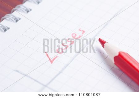 Notepad with handwritten word Losses by red pencil lying over paper sheet cold filtered shallow dept