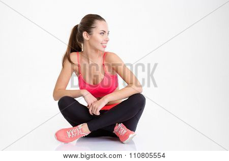 Happy smiling young fitness woman sitting with folded legs and looking away isolated over white background