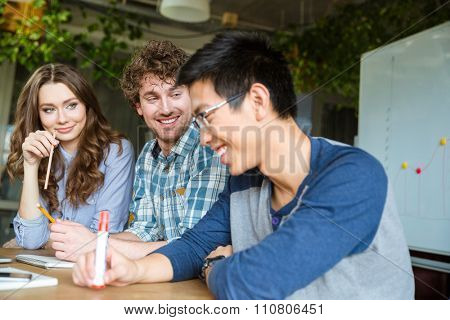 Young asian guy in glasses feels embarrassed and shy with his friends