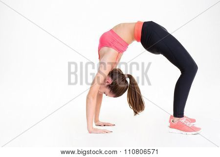 Beautiful young sportswoman doing back bend and stretching her back over white background