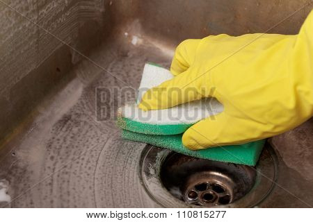 Cleaning a kitchen sink using cleaning sponge and cleaner