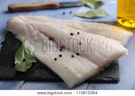 Raw Atlantic halibut fillet on a slate board