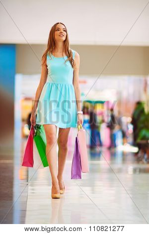 Pretty young shopper in blue dress and paperbags walking down mall