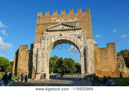 Tourists Walking Near The Ancient Arch Of Augustus (arco Di Augusto) In Rimini, Italy