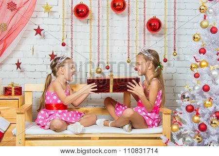Girls Sitting On A Bench In A Christmas Atmosphere And Keep The Big Red Gift In Hands