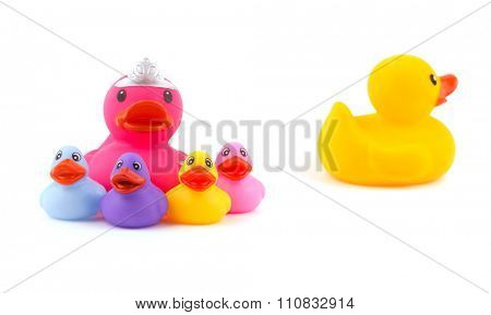 Mother rubber duck with children, with father leaving the group - concept of separation or divorce - on white