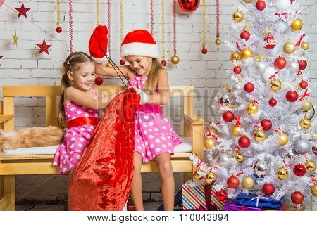 Two Girls Having Fun Trying To Untie The Bag With Gifts