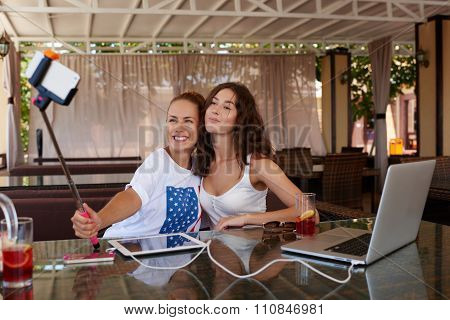 Smiling women photographing herself on cell telephone for social network picture