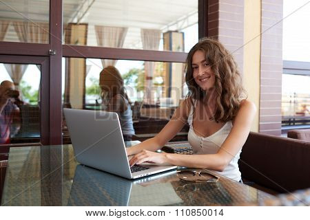 Portrait of a young smiling female freelancer using net-book for distance work in modern coffee shop