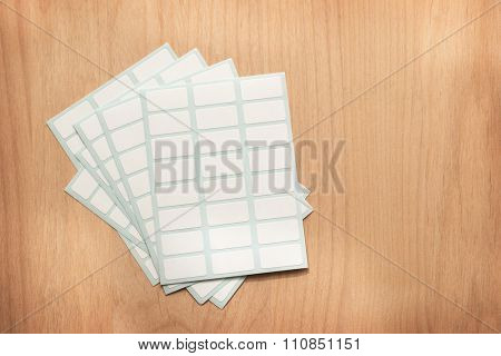 white labeling stickers with blue backing sheet, on a wooden table.